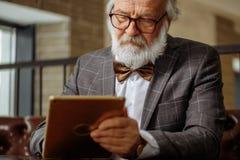 Le vieillard avec les cheveux blancs et la barbe clued tout au sujet des instruments Images stock