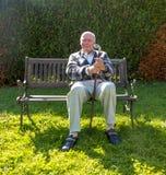 Le vieillard a plaisir à s'asseoir sur un banc dans son jardin image stock