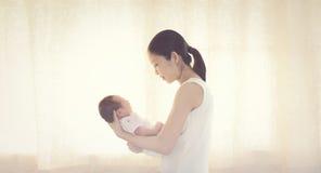 Le vieux bébé garçon asiatique de deux jours dans le confort des mamans arme Photo stock