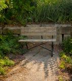 Le vieux banc de séance en bois placent stratégiquement dans un jardin Photo libre de droits