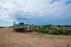 Le vieux bateau abandonné a lavé sur une plage Images stock
