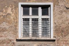 Le vieux blanc a encadré la fenêtre sur un vieux, ruiné bâtiment Photographie stock libre de droits