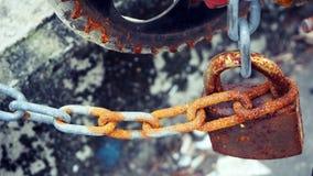 Le vieux cadenas avec une chaîne de fer à une barrière, déchets, confisquent, se rouillent image stock