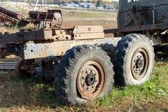 Le vieux camion cassé avec deux grandes roues abaissées contre le village avec les machines agricoles Photos stock