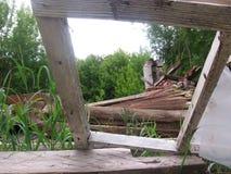 Le vieux châssis de fenêtre dans la maison en bois détruite a été plié cassé photographie stock