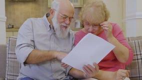 Le vieux couple vérifie leurs factures de loyer se reposant au sofa à la maison clips vidéos