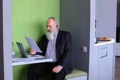 Le vieux directeur ou surveillant d'homme d'affaires calcule le balanc minimum photos stock