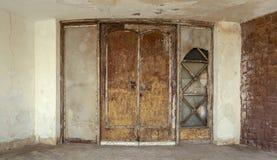Le vieux double en bois grunge abandonné laisse la porte et le mur de briques en pierre brun Image libre de droits