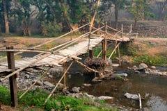 Le vieux et dangereux pont en bambou tribal croisent au-dessus de la rivi?re image stock
