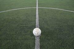 Le vieux football à donnent un coup de pied hors fonction le repère sur l'herbe fausse photo libre de droits