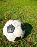 Le vieux football sur le champ d'herbe Photographie stock