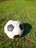 Le vieux football sur le champ d'herbe Photos stock