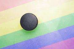 Le vieux galet d'hockey est sur la glace avec le drapeau gai Image stock