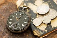 Le vieux livre, la vieille montre et l'argent Photographie stock libre de droits