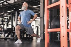 Le vieux mâle élégant apprécie la séance d'entraînement dans le gymnase moderne Images stock