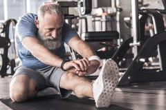 Le vieux mâle agréable est concentré sur ses exercices Images stock
