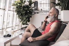 Le vieux mâle gai a la conversation agréable sur le smartphone Photographie stock libre de droits