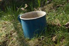 Le vieux métal d'émail a battu le jardin d'herbe de tasse photos stock