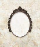 Le vieux métal ovale de cadre de tableau a travaillé au fond de marbre Images stock