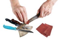 Le vieux maître plus âgé essaye d'affiler les couteaux de cuisine rouillés - isolant Photographie stock libre de droits