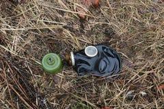 Le vieux masque de gaz se trouve sur l'herbe fanée après la pluie concept : biologique et intoxiquez le danger, l'extrémité du mo image stock