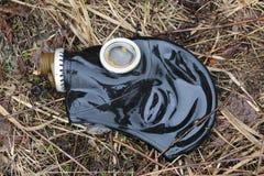 Le vieux masque de gaz se trouve sur l'herbe fanée après la pluie concept : biologique et intoxiquez le danger, l'extrémité du mo images stock