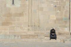 Le vieux moine seul dans des vêtements noirs s'assied sur des escaliers près de la vieille cathédrale orthodoxe en ville Mtskheta photos libres de droits
