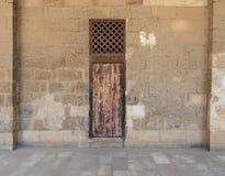 Le vieux mur de briques en pierre abandonné avec un a survécu à la porte en bois et à la fenêtre en bois de grille, le vieux Cair Photos libres de droits