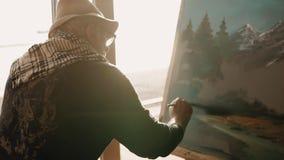Le vieux peintre seul peint un tableau avec le paysage dans son atelier banque de vidéos