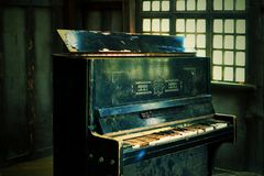 Le vieux piano cassé dans la maison en bois images stock