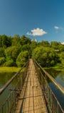 Le vieux pont de remorquage par la rivière d'Ural Photographie stock