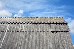 Le vieux toit d'amiante de toit slates contre le ciel bleu Photo libre de droits