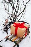 Le vieux traîneau en bois avec un cadeau dans le ruban rouge enveloppé d'or de cadeau de boîte de papier, sont dans la forêt d'hi Image libre de droits