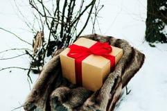Le vieux traîneau en bois avec un cadeau dans le ruban rouge enveloppé d'or de cadeau de boîte de papier, sont dans la forêt d'hi Image stock
