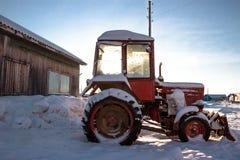 Le vieux tracteur rouge dans le village Photographie stock libre de droits