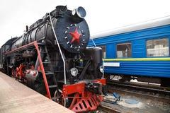 Le vieux train de vapeur part d'une gare Photos stock