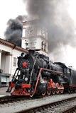 Le vieux train de vapeur part d'une gare Images libres de droits