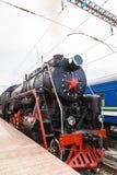 Le vieux train de vapeur part d'une station Photo stock