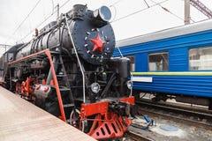 Le vieux train de vapeur part d'une station Photos stock