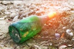 Le vieux vert de bouteille de vin se trouve sur le bord de mer dans le sable Photo stock