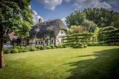 Le village anglais a couvert le cottage et le jardin de chaume Images stock