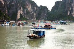Le village de flottement de Kuah blême près de l'île de Daw Guo dans Halong aboient au Vietnam Les bateaux authentiques nationaux Images libres de droits