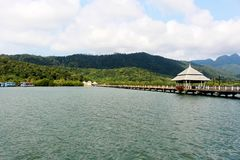 Le village de pêche regardent et le bateau de pêche avec le fond vert de montagne Photographie stock libre de droits