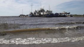 Le village de pêche sur la banque de la Mer du Nord, de vieux bateaux des pêcheurs et maisons en bois, Russie, le golfe de Finlan clips vidéos