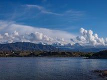 Le village est sur le rivage du lac au pied de neige-capp Photo stock