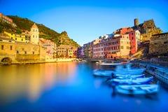 Le village, l'église, les bateaux et la mer de Vernazza hébergent sur le coucher du soleil. Cinque Image libre de droits
