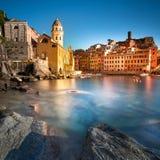 Le village, l'église, les roches et la mer de Vernazza hébergent sur le coucher du soleil Cinque Photos stock