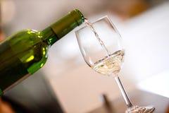 Le vin blanc échantillon versent dedans un verre image stock