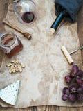 Le vin et l'apéritif ont placé avec l'espace de copie au centre Verre de vin rouge, bouteille, corkscrewer, fromage bleu, raisins Images libres de droits