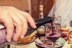 Le vin rouge coule dans le verre le soir au dîner avec des amis Images libres de droits